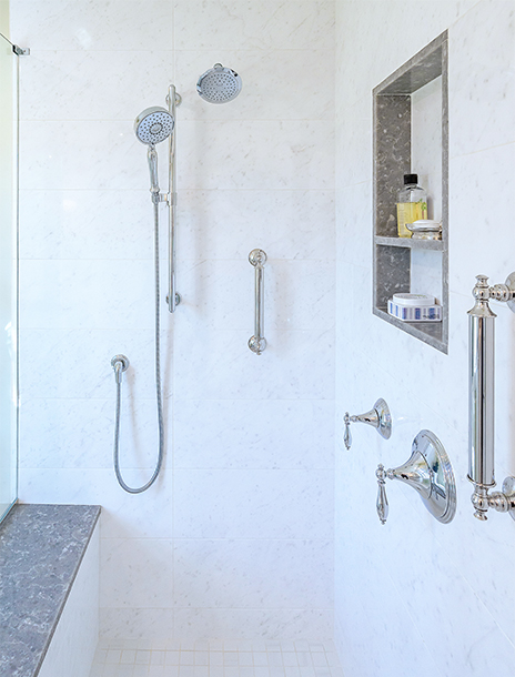 Shower in newly remodeled bathroom, featuring luxury shower heads, built-in shelving and grip bars