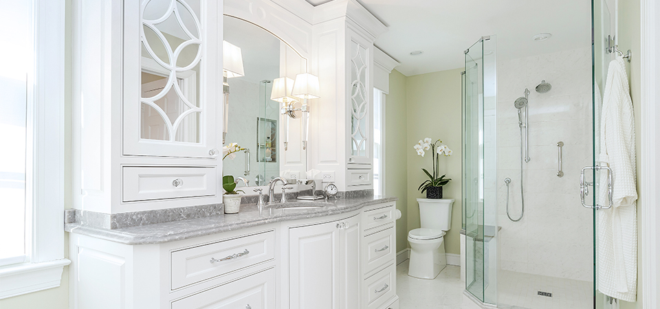 Completed bathroom remodeling project with white cabinets and glass walk-in shower